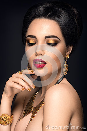 Beautiful woman portrait. Young lady posing with gold jewelry.