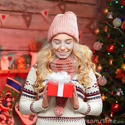 Portrait of a smiling cute woman opening gift box by christmas tree