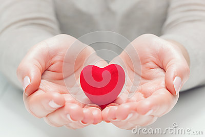 Small red heart in woman`s hands in a gesture of giving, protecting