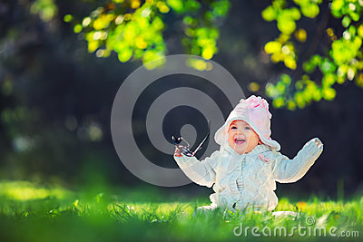 Beautiful smiling baby girl sitting on green grass