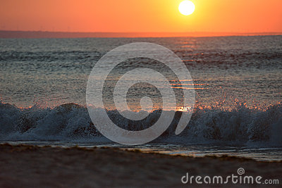 Early morning, the image of the sea at the sunrise. Waves, red s