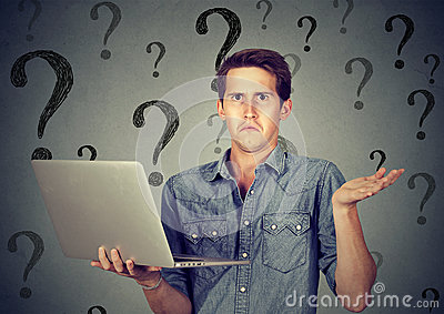 Perplexed man with laptop many questions and no answer