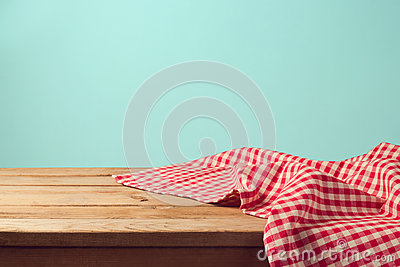 Empty wooden deck table and red checked tablecloth