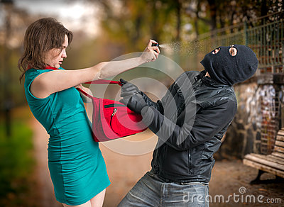 Self defense concept. Young woman was attacked by man in balaclava is using pepper spray