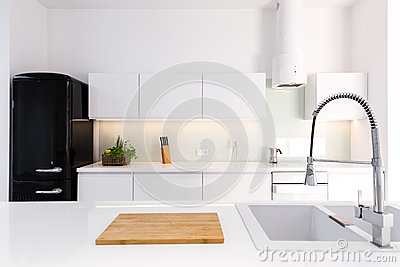 White, lacquer kitchen and black retro fridge