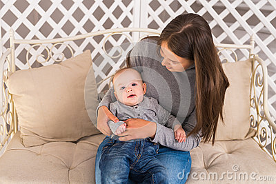 Young mother holding her newborn child. Mom nursing baby. Woman and new born boy in the room. Mother playing with