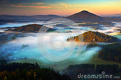 Czech typical autumn landscape. Hills and villages with foggy morning. Morning fall valley of Bohemian Switzerland park. Hills wit