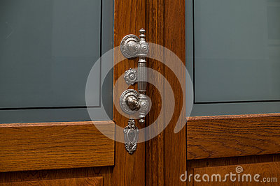 The old, metal doorhandle of a wooden door