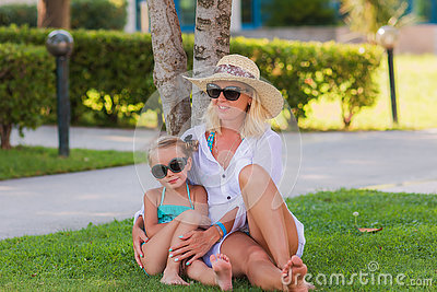 Mother and daughter sitting on green grass. They rest on holiday in Turkey
