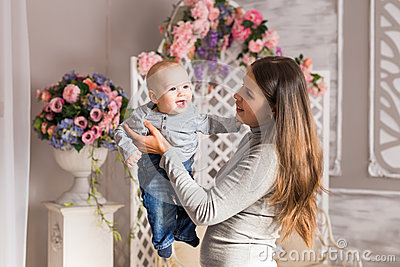 Young mother woman holding and hugging in her arms child baby kid boy smilling laughing