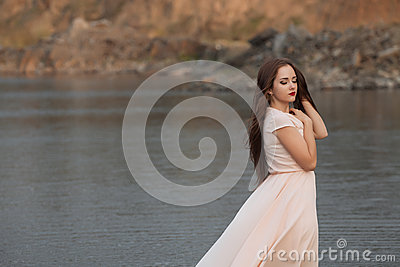 Portrait of the beautiful young woman with long brown hair pink flower posing at studio over dark background