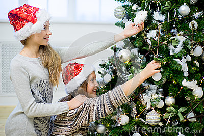 Two girls decorate the Christmas tree