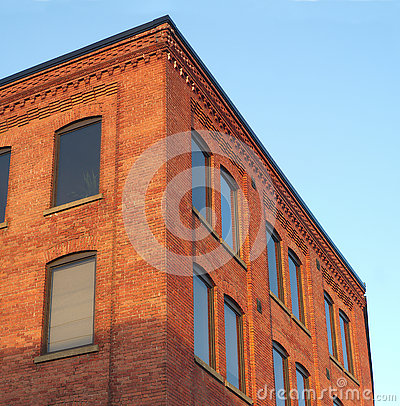 Red brick office building corner in sunlight blue sky