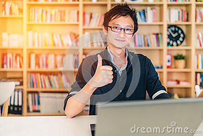 Young adult Asian man with laptop, thumbs up ok sign, home office or library scene, with copy space, success or technology concept