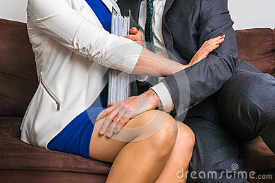 Man touching woman`s knee - sexual harassment in office