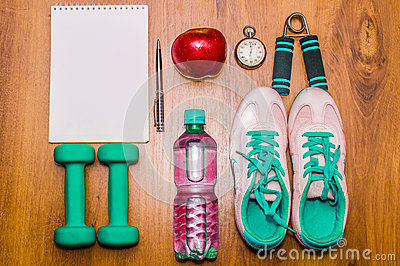 Workout and fitness dieting copy space diary. Healthy lifestyle concept. Dumbbell, water, expander hand  ball on rustic