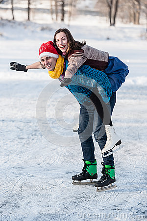 Happy couple having fun ice skating on rink outdoors.