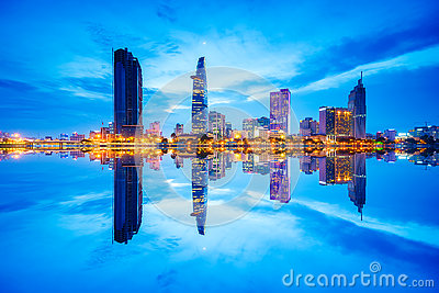 Cityscape in reflection of Ho Chi Minh city at beautiful twilight, viewed over Saigon river.