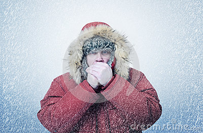 Frozen man in winter clothes warming hands, cold, snow, blizzard
