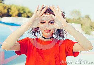 Love. Portrait smiling happy young redhead woman, making heart sign, symbol with hands. Positive human emotion expression feeling