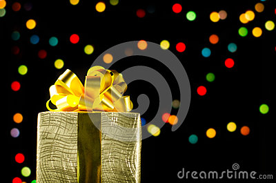 Gold christmas gift box with ribbon and bow on bokeh lights background