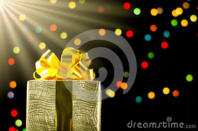 Gold christmas gift box with ribbon and bow on bokeh lights back