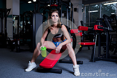 Sexy fitness woman in sportswear resting after dumbbells exercises in gym. Beautiful girl with perfect fitness body drinking from