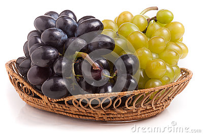 Bunch of green and blue grapes in wicker basket isolated on white background