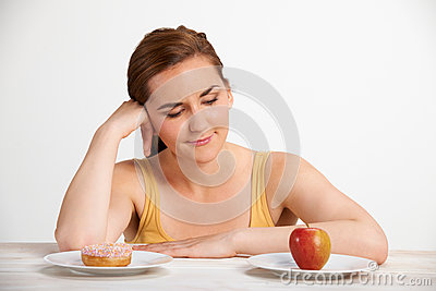 Woman Choosing Between Apple And Doughnut For Snack