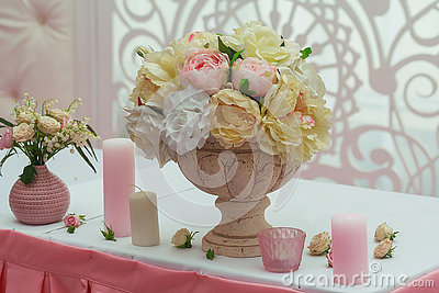 Roses in a vase and candles on the table