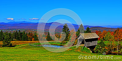 19th Century covered bridge in rolling green mountains of Vermont HDR.