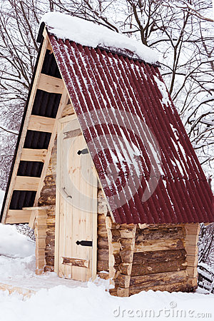 Wooden house from log, with red roof in winter forest
