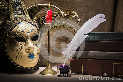 Vintage still life with old books near inkstand, feather, venezian mask and burning red candle in candlestick on canvas background