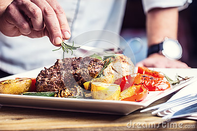 Chef in hotel or restaurant kitchen cooking only hands. Prepared beef steak with vegetable decoration