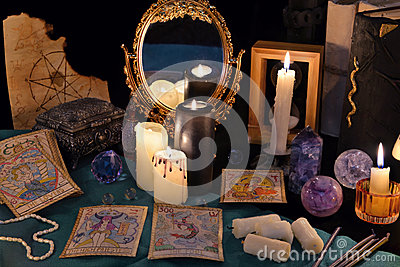 Divination rite with candles, the tarot cards, mirrow and crystals
