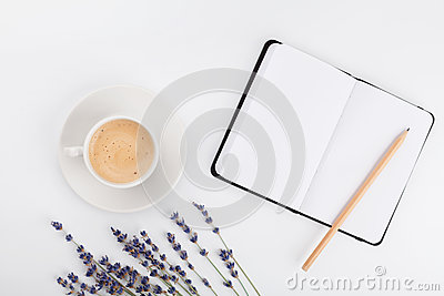 Coffee, clean notebook and lavender flower on white table from above. Woman working desk. Cozy breakfast. Mockup. Flat lay style.