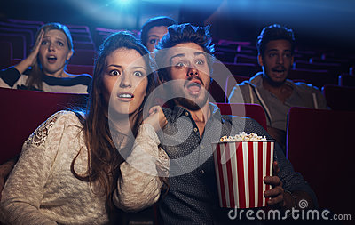 Young couple at the cinema watching an horror movie