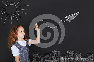 Cute girl throwing paper airplane near blackboard.