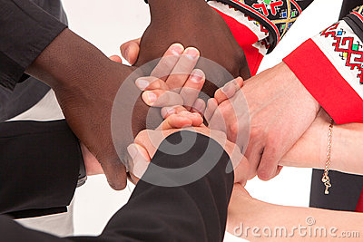 People of different nationalities and religions hold hands.
