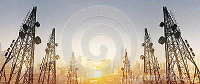 Silhouette, telecommunication towers with TV antennas and satellite dish in sunset, with double exposure city in sunrise backgroun