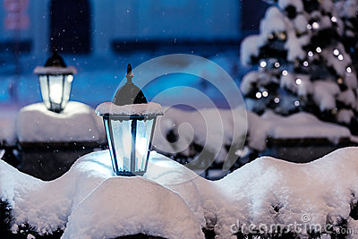 Snowy street lamps in night city with fir-tree and christmas lig