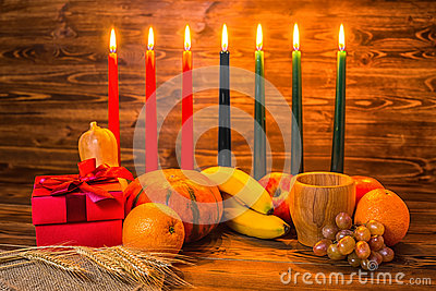 Kwanzaa holiday concept with traditional lit candles, gift box,