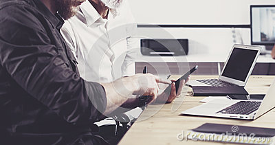 Concept of business people meeting process.Bearded young man holding mobile phone and touching screen.Adult businessman