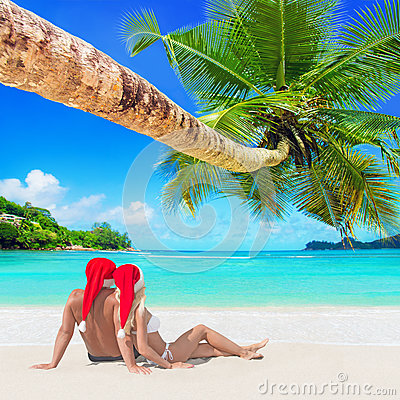 Romantic couple in red Christmas Santa hats sunbathe at tropical palm sandy island beach
