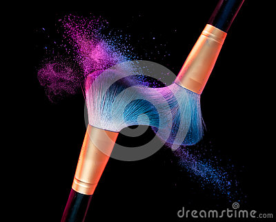 Makeup brush with blue powder explosion on black