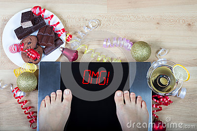 Digital scales with woman feet on them and sign sign`OMG!` surrounded by christmas decorations and unhealthy food