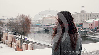 Back view. Attractive young brunette girl standing on the bridge and looks at the snow-covered winter town.