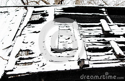Black and white photo snowy abandoned burned-out fire wooden house.