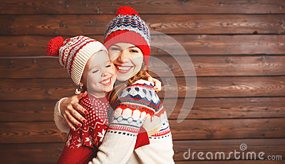 Happy family mother and child girl with christmas hat hugs at wo
