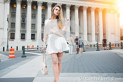 Fashionable city girl concept. Gorgeous young woman walking near city building wearing summer outfit clothes